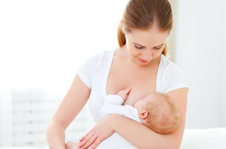 amamantando: madre amamantando a su bebé recién nacido en una cama blanca