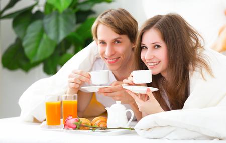 enamorados en la cama: pareja de enamorados que desayunan en cama en el D�a de San Valent�n