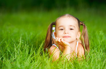 happy child little girl in a white dress lying on the grass Summer