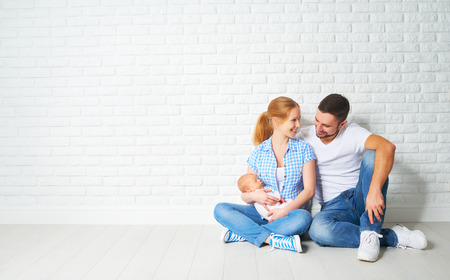 happy family mother and father of a newborn baby sitting on the floor near the blank brick wall Archivio Fotografico