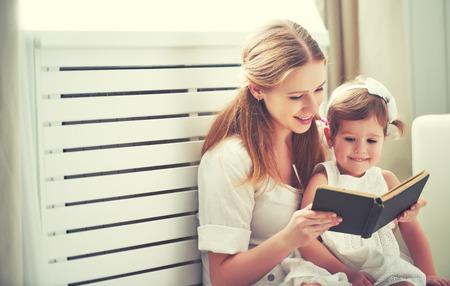 ni�os leyendo: hija ni�o feliz madre de familia ni�a que lee un libro por la ventana