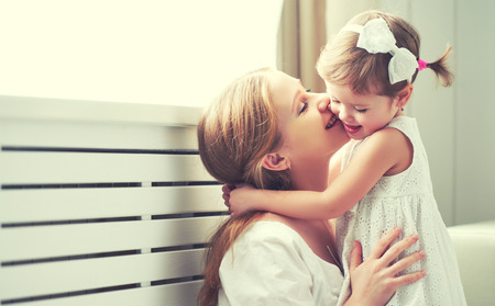 hugs and kisses: Happy loving family. mother and child girl playing, kissing and hugging