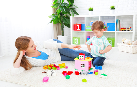 preschooler: Mother and child daughter playing together, build from the constructor