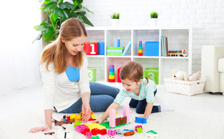 parents with baby: Mother and child daughter playing together, build from the constructor