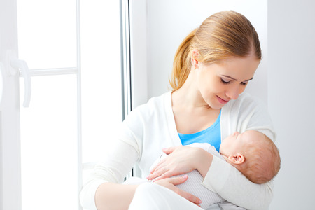 newborn baby in a tender embrace of mother at the window Stock Photo - 50959338