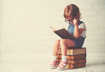 little girl child: happy child little girl with glasses reading a books