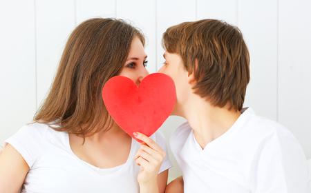 amantes en la cama: concepto para el día de San Valentín. pareja amante besando con un corazón rojo en la cama Foto de archivo