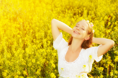 woman sunset: Happy woman enjoying the summer outdoors in the meadow of yellow flowers