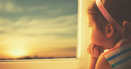 child sad little girl looking out the window at the sunset