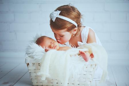 children sister kisses brother  newborn sleepy  baby on a light background Standard-Bild