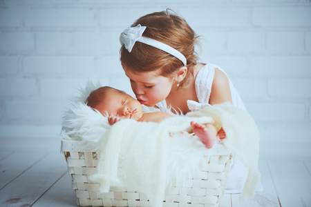 children sister kisses brother  newborn sleepy  baby on a light background Stockfoto