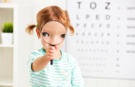 examen de la vista: concepto de prueba de visión. Chica niño con una lupa en el oftalmólogo médico