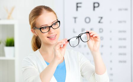 eyesight check. woman choose glasses at the doctor ophthalmologist optician Stock Photo