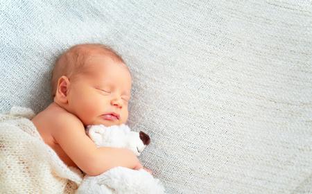 kisbabák: Aranyos újszülött alszik a játékot mackóval fehér Stock fotó