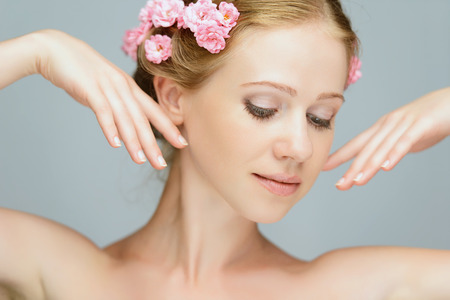 flower head: Beauty face of the young beautiful woman with pink flowers in her hair Stock Photo