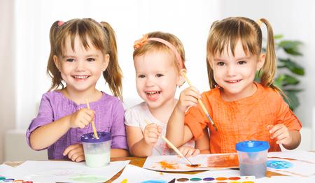 infant school: happy sister little girls in kindergarten draw paints