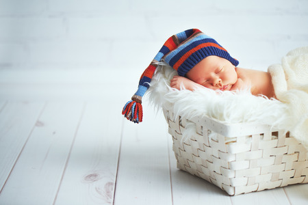 naked child: Cute happy newborn baby in a blue knit cap sleeping in a basket