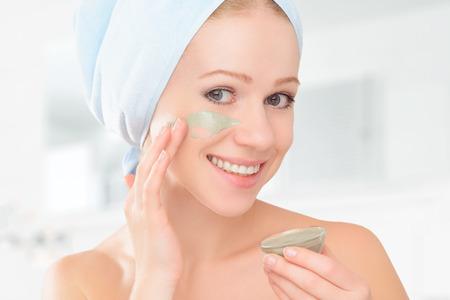 masaje facial: hermosa chica en el baño y la máscara facial para el cuidado de la piel Foto de archivo