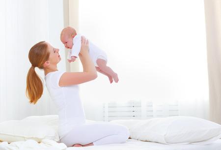 gelukkig gezin moeder spelen in bed met pasgeboren baby
