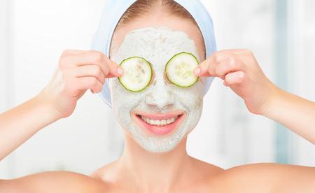 Grappig jong meisje met een masker voor de huid gezicht en komkommers op de ogen