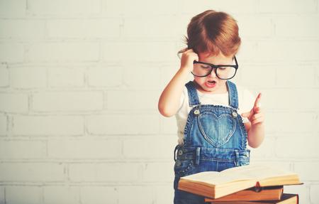 colegiala: ni�o ni�a feliz con gafas de leer un par de libros Foto de archivo