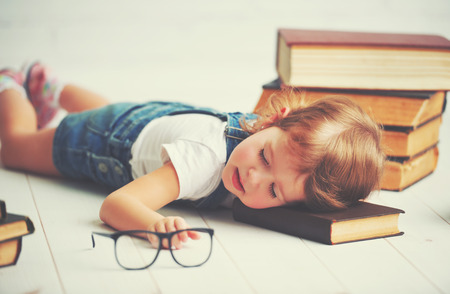 tired child little girl fell asleep for books