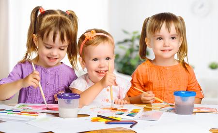 kinder: felices hermanas niñas en el jardín de infantes pinturas del drenaje