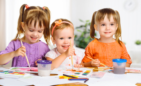 kindergarten education: happy sister little girls in kindergarten draw paints