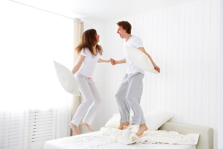 jumping: Happy loving couple jumping and having fun in bed
