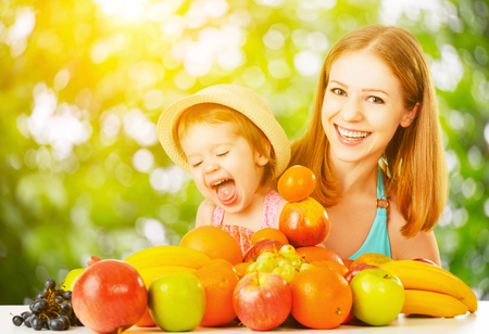 summer fruits: healthy vegetarian food. happy family mother and baby daughter with summer fruit