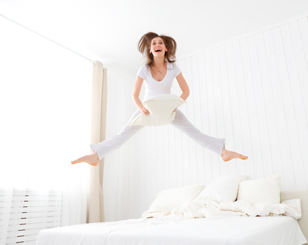 funny happy girl jumping and having fun in bed Stock Photo