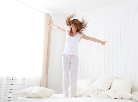 mujer en la cama: divertida niña saltando feliz y divertirse en la cama