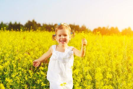 fiori di campo: bambina felice bambino in un abito bianco in esecuzione sul campo con un mazzo di fiori gialli, fiori di campo Archivio Fotografico