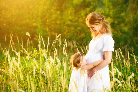 summer nature: happy family, a pregnant mother and daughter little girl child in the summer  meadow with yellow flowers