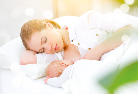 sleeping together and breastfeeding mother and her newborn baby in a white bed Foto de archivo