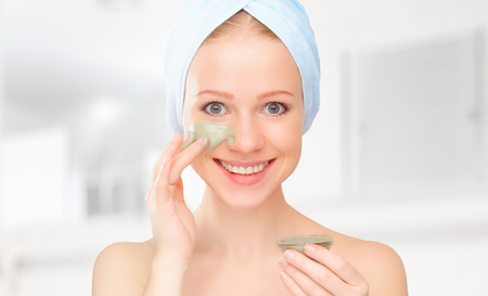 face mask: beautiful girl in the bathroom and mask for facial skin care