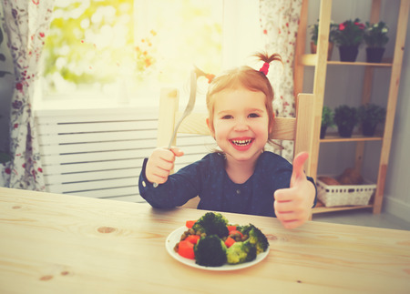 kids eating healthy: happy child girl loves to eat vegetables and showing thumbs up Stock Photo