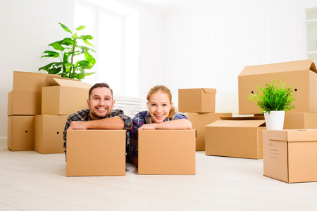 karton: moving to a new apartment. Happy family couple and a lot of cardboard boxes.