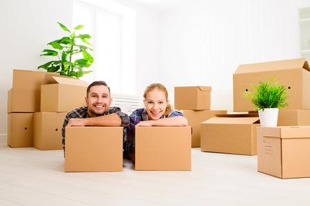 cajas de carton: mudarse a un nuevo apartamento. Pareja feliz de la familia y un montón de cajas de cartón.