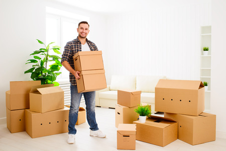 boy smiling: moving to a new apartment. Young happy man with cardboard boxes