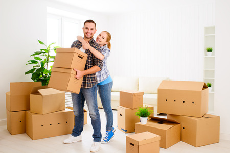 house property: moving to a new apartment. Happy family couple and a lot of cardboard boxes.