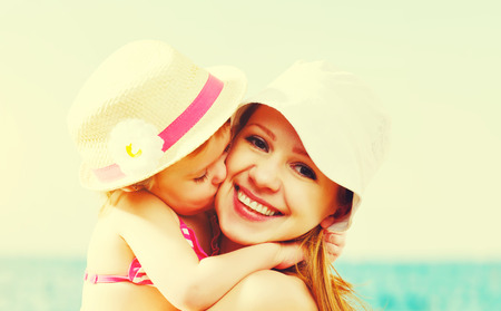 happy mom: happy family on the beach. baby daughter kissing mother  at sea