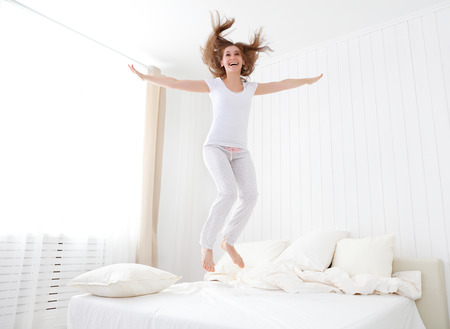 cushions: funny happy girl jumping and having fun in bed Stock Photo
