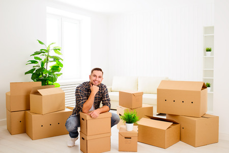 moving house: moving to a new apartment. Young happy man with cardboard boxes