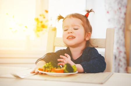 kind meisje houdt niet van en wil niet om groenten te eten Stockfoto