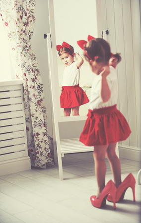 skirts: little girl child fashionista looking in the mirror at home in a red skirt, shoes of mother