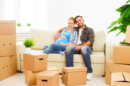 Umzug in eine neue Wohnung. junge Familie schwangere Frau und Ehemann mit Kartons