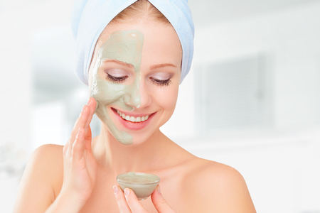 mujer maquillandose: hermosa chica en el baño y la máscara facial para el cuidado de la piel Foto de archivo