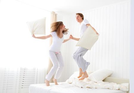 Gelukkig verliefde paar springen en plezier in bed