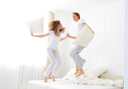 Happy loving couple jumping and having fun in bed